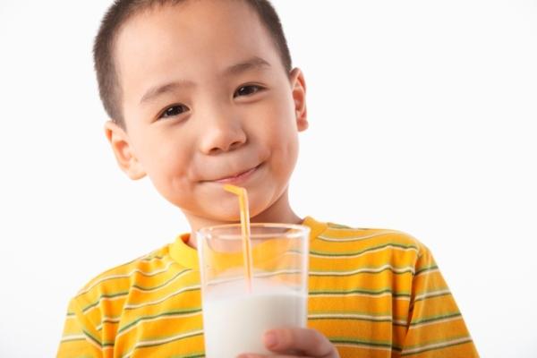 Boy (5-7) drinking milk
